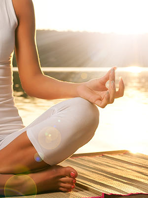 Image of a young woman in a yoga pose meditating with the sun in the background that links to webpage outlining services provided for employee benefits.