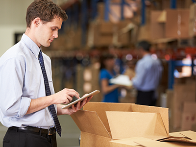 Young man in a warehouse using an iPad to check boxes in inventory.