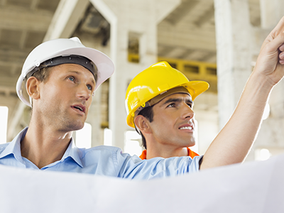 Two men wearing hardhats on a construction site, one man is pointing to a location out of view.