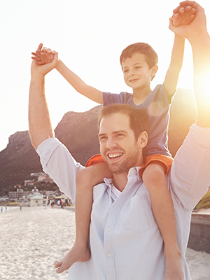Image of a father with his son sitting on his shoulders having fun on the beach, links to webpage outlining personal lines and private client services provided.