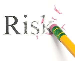 A number 2 pencil erasing the word Risk from a white piece of paper.